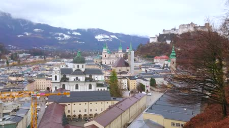 vítr : SALZBURG, AUSTRIA - MARCH 1, 2019: Rainy cityscape with Collegiate Church (Kollegienkirche), old town roofs, belfries, domes and Hohensalzburg Castle on Festungsberg Hill, on March 1 in Salzburg Dostupné videozáznamy