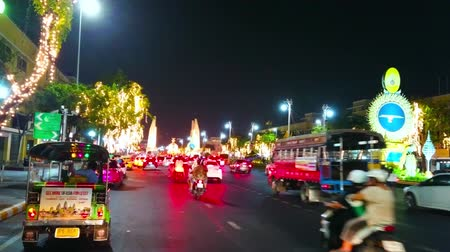 semt : BANGKOK, THAILAND - MAY 11, 2019: Busy evening Ratchadamnoen Avenue with driving cars, tuk tuks, bikes, installations due to Coronation Ceremony, Democracy Monument on background, on May 11 in Bangkok
