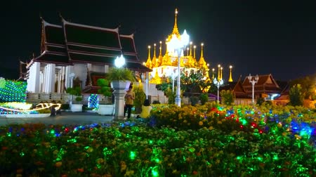 BANGKOK, THAILAND - MAY 11, 2019: The lighting garlands in flower bed of Mahajetsadabadin park overlooking the shrines of Wat Ratchanatdaram, on May 11 in Bangkok