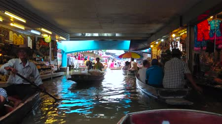 ratchaburi : DAMNOEN SADUAK, THAILAND - MAY 13, 2019: The sampans (boats) float under the bridge through the narrow canal of Ton Khem floating market with many small souvenir stalls, on May 13 in Damnoen Saduak Stock Footage