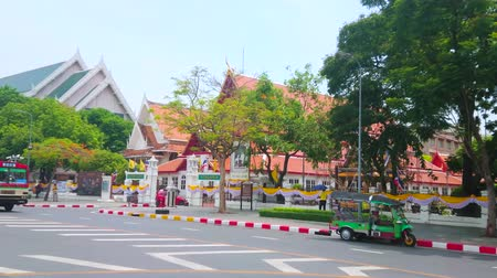 pavilion : BANGKOK, THAILAND - APRIL 15, 2019: The red tile roof of Siwamokkhaphiman Hall of National Museum through the spread trees of Na Phra That Alley, on April 15 in Bangkok Stock Footage