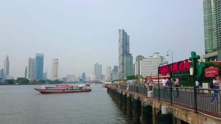 паром : BANGKOK, THAILAND - MAY 15, 2019: The view from the pier of Asiatique the Riverfront Shopping Center on the Chao Phraya river, modern skyscrapers and floating boats, on May 15 in Bangkok