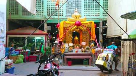 composição : BANGKOK, THAILAND - APRIL 23, 2019: The golden shrine with King statue in courtyard of Yodpiman (Pak Khlong Talat) flower market, on April 23 in Bangkok Stock Footage