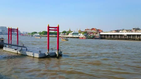 паром : BANGKOK, THAILAND - APRIL 23, 2019: The Chao Phraya river with red piles of floating pier at Wat Arun temple, fast boats and spires of Wat Pho on the opposite bank, on April 23 in Bangkok
