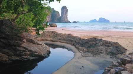 The stunning landscape from the Tonsai Bay coast with a view on narrow winding creek, tropical greenery, sand beach and tall rock of Ao Nang Tower, Krabi, Thailand