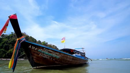 indianin : AO NANG, THAILAND - APRIL 25, 2019: Traditional wooden longtail boat with colorful ribbons is rocking on the coast of central beach, on April 25 in Ao Nang Wideo