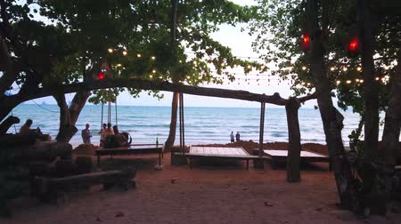 indianin : AO NANG, THAILAND - APRIL 25, 2019: The best way to spend romantic evening is to visit comfortable beach bar with line of sunbeds and relax on coast, on April 25 in Ao Nang