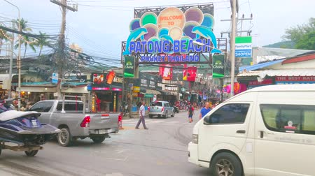 siamês : PATONG, THAILAND - MAY 1, 2019: Heavy traffic in tourist street with souvenir stores, market stalls, cafes, bars and travel agencies, large colorful boards and signs on background, on May 1 in Patong Stock Footage