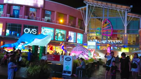 украшенный : PATONG, THAILAND - MAY 1, 2019: The crowded area in front of modern Jungceylon shopping center, decorated with installation of dolphins and blue whale, on May 1 in Patong Стоковые видеозаписи