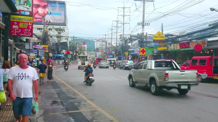 semt : PATONG, THAILAND - APRIL 29, 2019: The busy tourist street of resort with driving cars, numerous cafes, shops, drug stores and other tourist facilities, on April 29 in Patong Stok Video