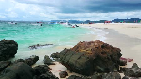 stone : PHUKET, THAILAND - MAY 1, 2019: Amazing white sand beach of Khai Nai island with a view on massive boulders, moored speed boats and watercrafts on the background, on May 1 on Phuket