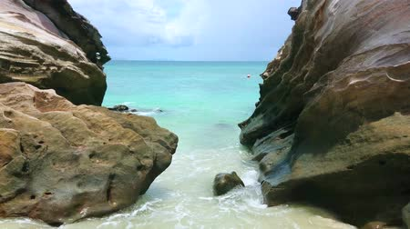 stone : The foamy waves washes the sand between the boulders on the shore of Khai Nai island, Phuket, Thailand Stock Footage