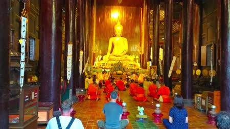 kolumna : CHIANG MAI, THAILAND - MAY 2, 2019: The worship in medieval teak Wat Phan Tao temple; bhikkhu monks sit in front of the altar and the Buddhist devotees are behind them, on May 2 in Chiang