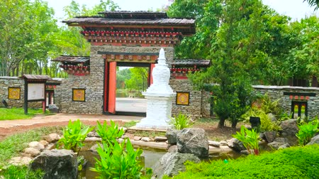украшенный : CHIANG MAI, THAILAND - MAY 7, 2019: Explore Bhutan Garden in Rajapruek Royal Park, it boasts stone gate, decorated with carved wood and white Buddhist chorten in front of gate, on May 7 in Chiang Mai