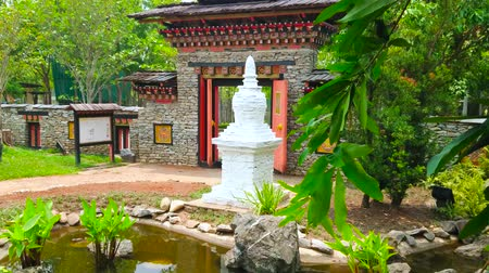 bhutan : CHIANG MAI, THAILAND - MAY 7, 2019: White chorten (stupa) at the pond in Bhutan Garden of Rajapruek Royal Park; ornate gate with colored wooden carvings located on background, on May 7 in Chiang Ma
