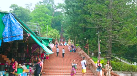 言うこと : CHIANG MAI, THAILAND - MAY 7, 2019: The tourist market at the slope of Doi Suthep Mountain with long staircase, leading to the Wat Phra That Doi Suthep temple, on May 7 in Chiang Mai 動画素材