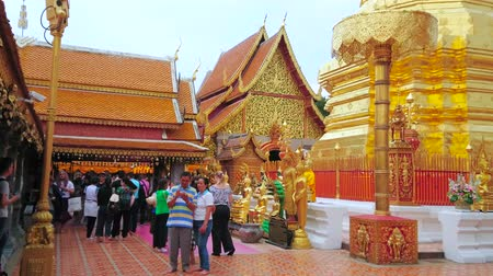 mold : CHIANG MAI, THAILAND - MAY 7, 2019: Crowded court of Wat Phra That Doi Suthep golden temple, tourists make photos and explore the beauty of chedi, chatra umbrellas and shrines, on May 7 in Chiang Mai Stock Footage