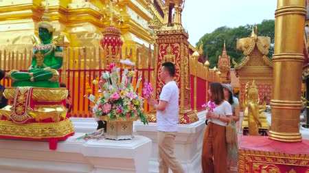 buquê : CHIANG MAI, THAILAND - MAY 7, 2019: The group of pilgrims prays, walking around the great golden chedi of Wat Phra That Doi Suthep golden temple, on May 7 in Chiang Mai