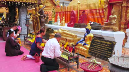templo : CHIANG MAI, THAILAND - MAY 7, 2019: Pilgrims pray at the altar with candles and incense sticks in court of Wat Phra That Doi Suthep golden temple, on May 7 in Chiang Mai