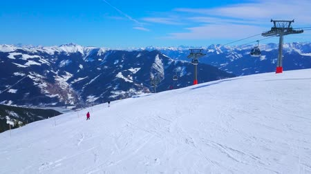 trilhas : ZELL AM SEE, AUSTRIA - FEBRUARY 28, 2019: Enjoy the Alpine sceniery from the white slope of Schmitten mount with a view on skiers and riding Trassxpress cable car, on February 28 in Zell Am See Vídeos