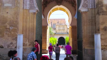mór : CORDOBA, SPAIN - SEPTEMBER 30, 2019: Busy pass through the medieval Puerta del Perdon (Forgiveness Gate) of Mezquita-Catedral with horseshoe arch and ruins of Roman columns, on September 30 in Cordoba