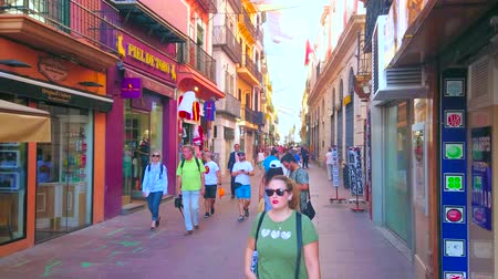 menigte : SEVILLE, SPAIN - OCTOBER 1, 2019: Calle Sierpes is one of the main shopping streets in Casco Antiguo historic district, its famous for the brand stores, cafes and galleries, on October 1 in Seville Stockvideo