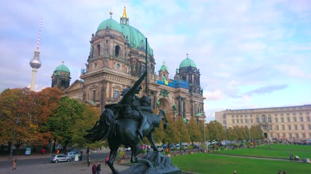 torre sineira : BERLIN, GERMANY - OCTOBER 3, 2019: The bronze sculpture of Amazon, fighting the lioness with a view on Cathedral on the background, on October 3 in Berlin Stock Footage