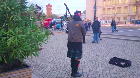 kolumna : BERLIN, GERMANY - OCTOBER 3, 2019: Performance of the street musician in Highland dress, playing bagpipes on Museum Island, on October 3 in Berlin
