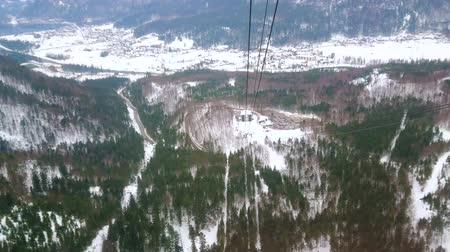 air vehicle : OBERTRAUN, AUSTRIA - FEBRUARY 21, 2019: Dachstein-Krippenstein air tram ride with a view on winter forests, Alpine landscape and Traun river valley, on February 21 in Obertraun Stock Footage
