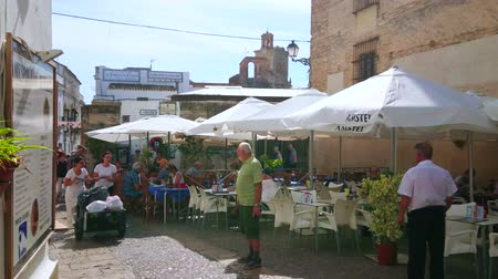 Андалусия : ARCOS, SPAIN - SEPTEMBER 23, 2019: Extremely small and busy Plaza Boticas square with walking people, cars and tables of cafe at the wall of medieval Mercedarian Nuns Convent, on September 23 in Arcos
