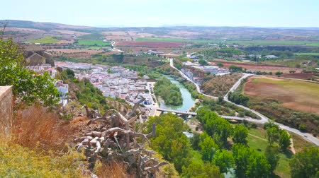 Enjoy aerial view on Guadalete river valley with historic white housing of Arcos, agricultural lands, lush greenery and mountains on the background, Andalusia, Spain Stock mozgókép