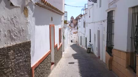 Андалусия : ARCOS, SPAIN - SEPTEMBER 23, 2019: The descent through the medieval Calle Altozano street with long rows of white residential houses, on September 23 in Arcos Стоковые видеозаписи