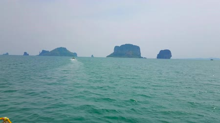 indianin : Enjoy boat trip to impressive islands of Krabi region - Koh Poda Island, Chicken Island (Koh Kai), Ko Ya Wa Bong Ko Island and other rocky formations dominate the skyline above Andaman sea, Thailand