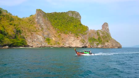 aonang : AO NANG, THAILAND - APRIL 26, 2019: The old longtail boat floats along the coast of spectacular Chicken Island (Koh Kai), famous for its unique rocky shape and nice beaches, on April 26 in Ao Nang