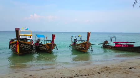 sudeste : AO NANG, THAILAND - APRIL 26, 2019: The old longtail boats are rocking on the tide waves at the beach of Koh Poda Island, on April 26 in Ao Nang