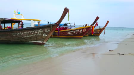 украшенный : AO NANG, THAILAND - APRIL 26, 2019: The tide line of  Koh Poda Island with a view on sandy coast and moored longtail boats, decorated with colorful ribbons, flowers and signs, on April 26 in Ao Nang
