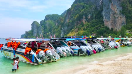 takımadalar : PHIPHI DON, THAILAND - APRIL 27, 2019: The Tonsai Bay of Phi Phi Don Island with line of speed boats, moored along the white sandy shore and the tall rocks on the background, on April 27 in PhiPhi Don Stok Video