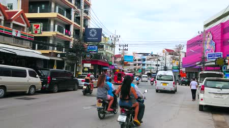 siamês : PATONG, THAILAND - APRIL 30, 2019: The traffic in wide street with modern housing, numerous cafes, shops, drug stores and other tourist facilities, on April 30 in Patong Stock Footage
