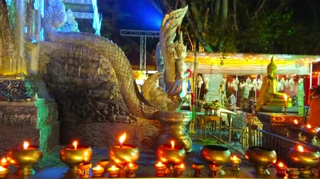 ganesha : CHIANG MAI, THAILAND - MAY 4, 2019: The gilt bowls with burning candles in front of engraved balluster of Silver Temple (Wat Sri Suphan), topped with sculpture of Naga serpent, on May 4 in Chiang Mai