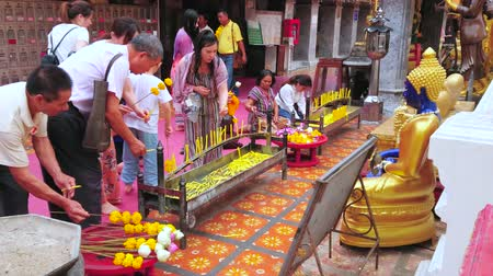 buquê : CHIANG MAI, THAILAND - MAY 7, 2019: The pilgrims pray at the golden Buddha altar in medieval Wat Phra That Doi Suthep temple, on May 7 in Chiang Mai