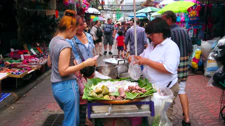마구간 : BANGKOK, THAILAND - MAY 12, 2019: The crowded Mangkon Road, lined with Chinatown market stalls and food cart amid the alley, offering banana wraps and boiled rice with vegetables, on May 12 in Bangkok