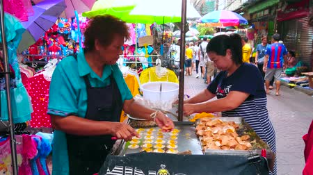 bairro : BANGKOK, THAILAND - MAY 12, 2019: Cooking of Thai crispy pancakes (khanom buang) in food cart, located in Mangkon Road of Chinatown market, on May 12 in Bangkok Stock Footage