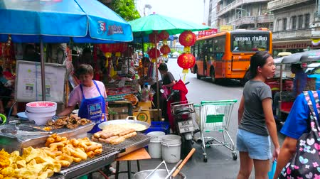 grillowanie : BANGKOK, THAILAND - MAY 12, 2019: Yaowarat roadside stall in Chinatown with cook, preparing deep fried puffs, crispy pancakes, grilled meat in kitchen with oven, wok and BBQ, on May 12 in Bangkok