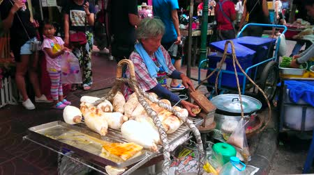 carrello spesa : BANGKOK, THAILAND - MAY 12, 2019: The elderly farmer cooks boiled taro roots in small outdoor stall, located in Yaowarat of Chinatown market, on May 12 in Bangkok