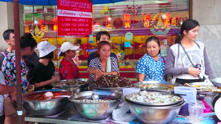 carrello spesa : BANGKOK, THAILAND - MAY 12, 2019: Chinatown market stall in Yaowarat road offers wide range of salted and pickled seafood - octopusses, calamaries, prawns, sea snails, mussels, on May 12 in Bangkok Filmati Stock
