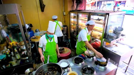 Çin mahallesi : BANGKOK, THAILAND - MAY 12, 2019: The open air kitchen of Chinese restaurant, experienced cooks prepare noodles in wok, sauces and soups, Yaowarat road, Chinatown, on May 12 in Bangkok