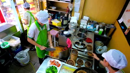 trouba : BANGKOK, THAILAND - MAY 12, 2019: The cook of Chinese restaurant cuts peking duck, the others prepare jiaozi dumplings in bamboo steamers, Yaowarat road, Chinatown, on May 12 in Bangkok