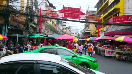 siamês : BANGKOK, THAILAND - MAY 12, 2019: Crowded pedestrian Yaowarat Road crosswalk at the gate of Itsara Nuphap street food market, full of carts, stalls and driving cars, Chinatown, on May 12 in Bangkok