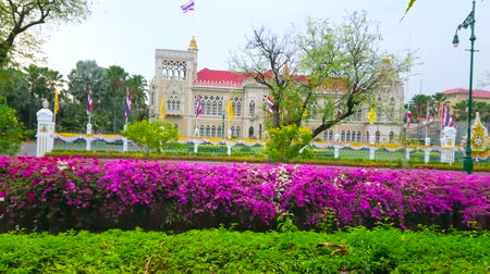 siamês : BANGKOK, THAILAND - MAY 13, 2019: The facade of Thai-Khu-Fah palace of Government House through the lush greenery and bougainvillea flowers around the Khlong Prem Prachakon canal, on May 13 in Bangkok