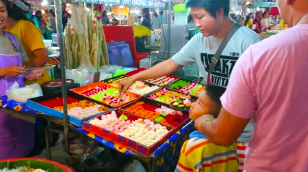 siamês : BANGKOK, THAILAND - MAY 13, 2019: The father with little kids chooses sushi rolls in stall of Talad Saphan Phut market, on May 13 in Bangkok